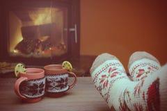 Pies en calcetines de lana por la chimenea de la Navidad La mujer se relaja Imagenes de archivo