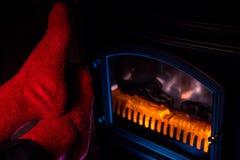 Pies en calcetines de lana rojos mullidos por la chimenea Imagen de archivo
