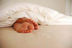 Pies en cama Fotografía de archivo libre de regalías