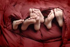Pies en cama Fotos de archivo