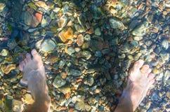 Pies en el agua Imagenes de archivo