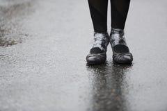 Pies en el asfalto mojado Imagen de archivo libre de regalías
