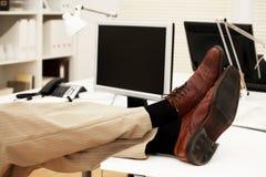 Pies en el escritorio de oficina Fotografía de archivo libre de regalías