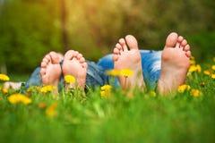 Pies en hierba. Comida campestre de la familia en parque de la primavera Fotos de archivo libres de regalías
