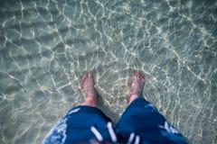 Pies en la agua de mar Fotografía de archivo