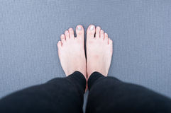 Pies en la estera de la yoga imagen de archivo
