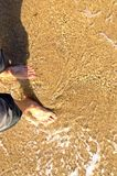 Pies en la playa arenosa Fotos de archivo