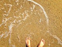 Pies en la playa arenosa Foto de archivo libre de regalías