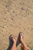 Pies en la playa con las conchas marinas Foto de archivo libre de regalías