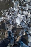 Pies en la playa con los pequeños icebergs Foto de archivo