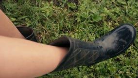 Pies en las botas de goma con suciedad en el lenguado metrajes