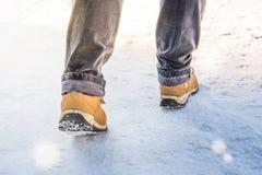 Pies en las botas que caminan en la nieve Fotos de archivo