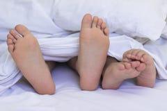 Pies en las hojas de cama Fotos de archivo libres de regalías
