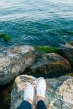 Pies en las zapatillas de deporte blancas que se colocan en la roca, hermosa vista del agua ondulada Imagenes de archivo