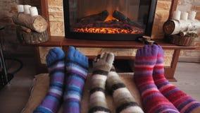 Pies en los calcetines divertidos de lana que se calientan por el fuego acogedor en tiempo de la Navidad almacen de video