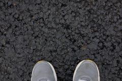 Pies en los zapatos en el nuevo asfalto imagenes de archivo