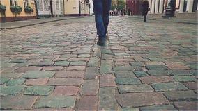 Pies en zapatos en las tejas de pavimentación, visión superior almacen de video
