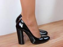 Pies femeninos calzados en zapatos negros con los talones en un fondo blanco que se coloca en el piso de madera Foto de archivo