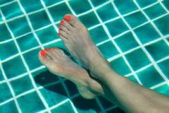 Pies femeninos con el polaco del rojo en los clavos del finger empapados en una piscina de agua en el verano Fotografía de archivo libre de regalías