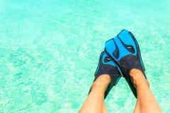 Pies femeninos con las aletas azules del snorkeler sobre el agua de azules turquesa Imágenes de archivo libres de regalías