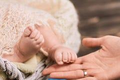 Pies femeninos de la mano y del bebé Foto de archivo
