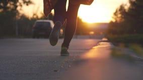 Pies femeninos de las piernas que corren en el parque durante puesta del sol hermosa Ejercicio de concepto 4k, 3840x2160 metrajes