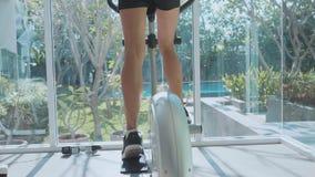 Pies femeninos del primer que montan en la bici inmóvil en el gimnasio metrajes