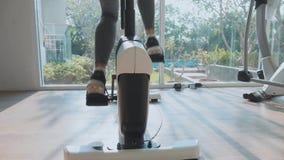 Pies femeninos del primer que montan en la bici inmóvil en el gimnasio en la cámara lenta almacen de metraje de vídeo