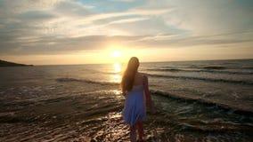 Pies femeninos del turista del caminante que caminan descalzo en orilla en la puesta del sol Las piernas de la mujer joven que va metrajes