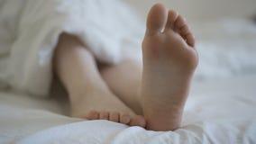 Pies femeninos delicados que mueven los dedos del pie juguetónamente en el lecho blanco almacen de metraje de vídeo