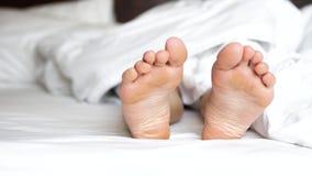 Pies femeninos delicados que mueven los dedos del pie juguetónamente en el lecho blanco almacen de video