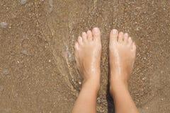 Pies femeninos descalzos en la espuma del mar Foto de archivo