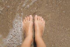 Pies femeninos descalzos en la espuma del mar Fotos de archivo libres de regalías