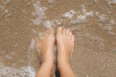 Pies femeninos descalzos en la espuma del mar Imagen de archivo