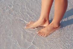 Pies femeninos en agua en la playa Foto de archivo libre de regalías