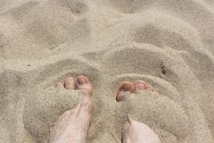 Pies femeninos en la arena Fotografía de archivo