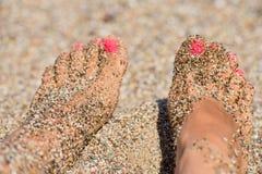 Pies femeninos en la arena Imagen de archivo libre de regalías