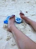 Pies femeninos en la playa arenosa con los deslizadores azules, holi de las vacaciones Imágenes de archivo libres de regalías