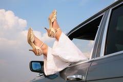 Pies femeninos en la ventana del coche Imagen de archivo