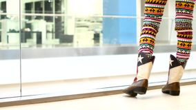 Pies femeninos en las botas de cuero Una muchacha se está colocando en un centro comercial almacen de video