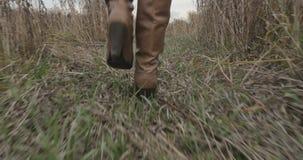 Pies femeninos en las botas que corren a lo largo del camino del otoño almacen de metraje de vídeo