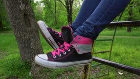 Pies femeninos en las zapatillas de deporte que se mueven y que presentan en parque de la primavera almacen de metraje de vídeo