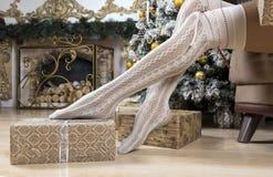 Pies femeninos en los calcetines del cordón, regalos en el papel de embalaje, una Navidad Fotos de archivo