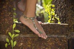 Pies femeninos en piedra con la pulsera en el tobillo Fotografía de archivo libre de regalías