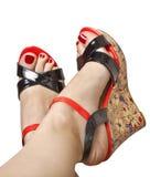 Pies femeninos en sandalias en un tacón de cuña Fotos de archivo libres de regalías