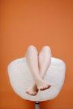 Pies femeninos en una butaca Foto de archivo libre de regalías