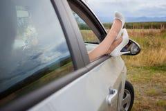 Pies femeninos en una ventanilla del coche Imagen de archivo