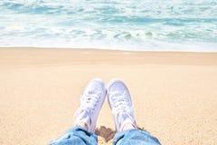 Pies femeninos en vaqueros y zapatillas de deporte blancas en la playa Caminata a lo largo de la playa imagen de archivo libre de regalías