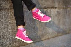 Pies femeninos en zapatillas de deporte rosadas Fotografía de archivo