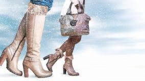 Pies femeninos en zapatos del invierno Foto de archivo